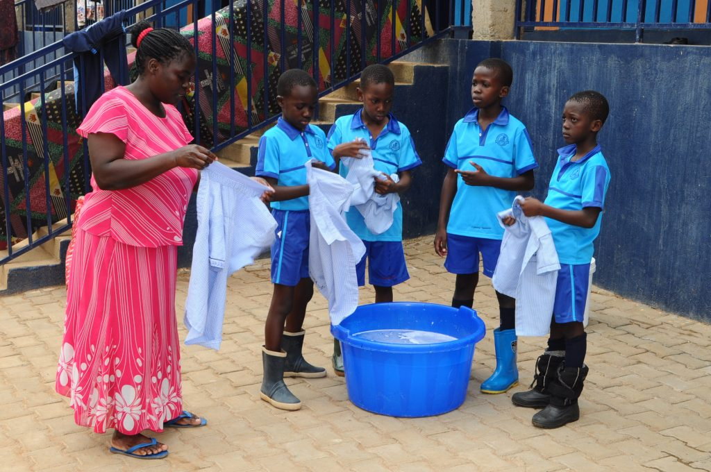 School staff inspecting pupils after washing in livelihood skills program