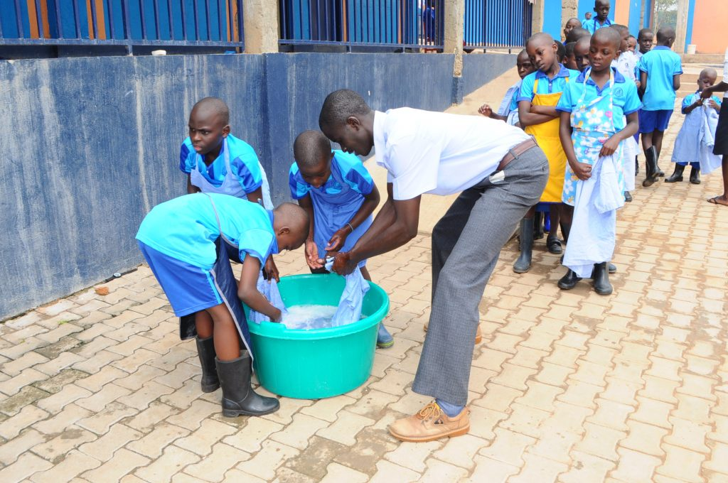 Teacher helps and teaches pupils to wash during the livelihood skills program